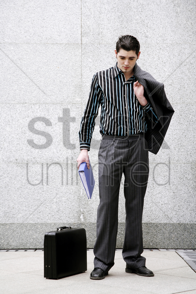 businessman holding his coat and a document stock photo