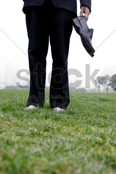 businessman holding his shoes stock photo