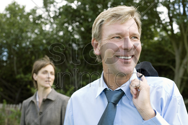 businessman holding his suit with businesswoman standing in the background stock photo