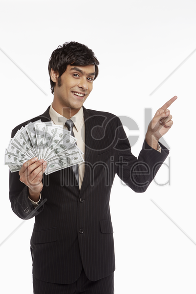 businessman holding money and pointing to the left stock photo