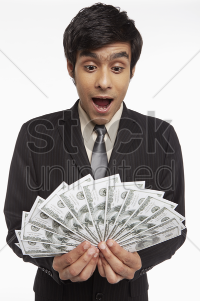 businessman holding money, looking surprised stock photo