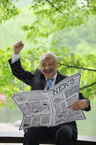 businessman holding newspaper and raising his hand stock photo