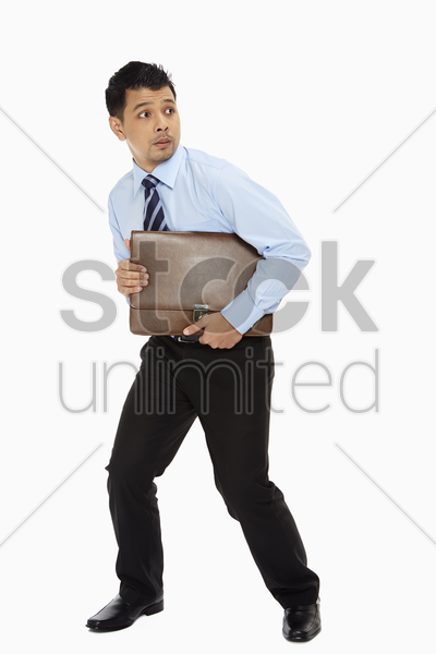businessman holding on tightly to his briefcase stock photo
