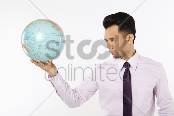 businessman holding on to a globe stock photo