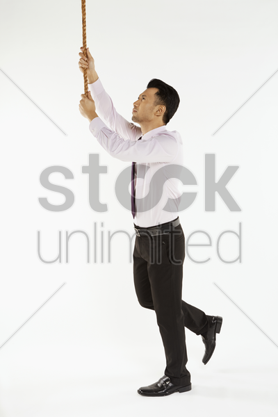 businessman holding on to a rope stock photo