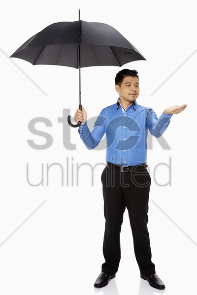 businessman holding out his hand while carrying an umbrella stock photo