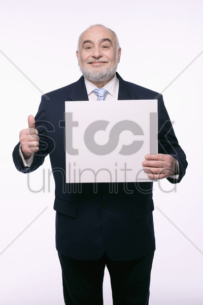 businessman holding placard and showing thumbs up stock photo