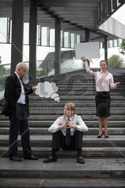 businessman holding thinking bubble above another businessman's head, businesswoman holding speech bubble stock photo