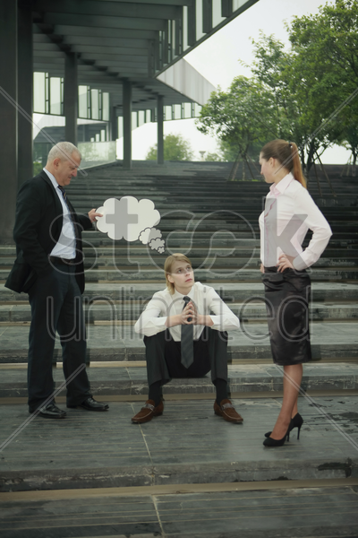 businessman holding thinking bubble above another businessman's head, businesswoman watching stock photo