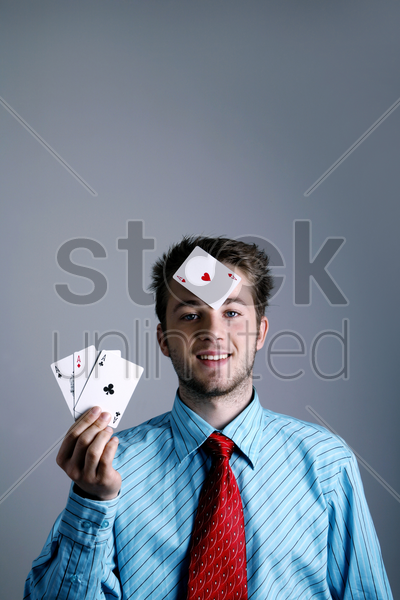 businessman holding three playing cards with another one on his forehead stock photo
