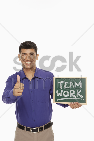 businessman holding up a blackboard with 'team work' written on it stock photo