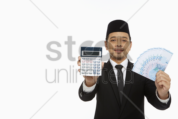 businessman holding up a calculator along with a pile of cash stock photo