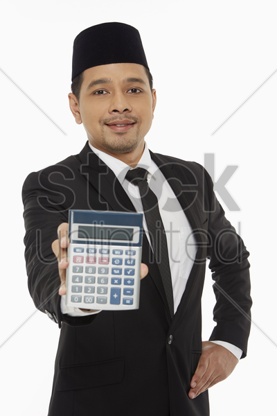 businessman holding up a calculator stock photo