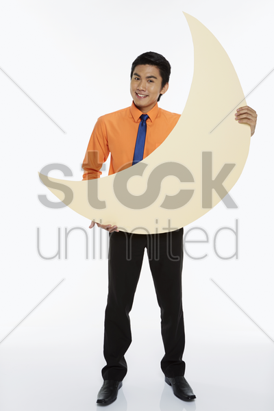 businessman holding up a crescent moon stock photo