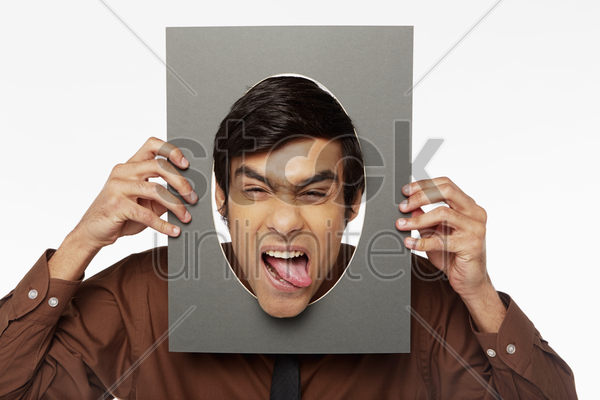 businessman holding up a cut out cardboard with hole, making faces stock photo