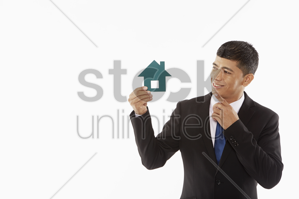 businessman holding up a cut out house, contemplating stock photo
