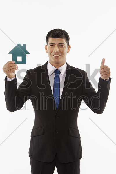 businessman holding up a cut out house, giving thumbs up stock photo