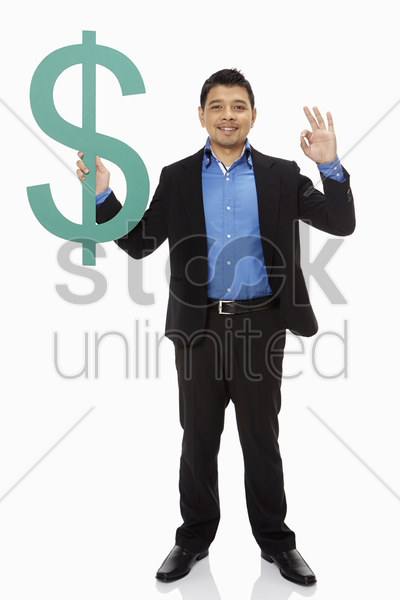 businessman holding up a dollar sign and showing hand gesture stock photo