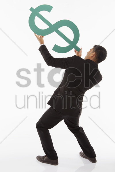 businessman holding up a dollar sign, showing shooting gesture stock photo