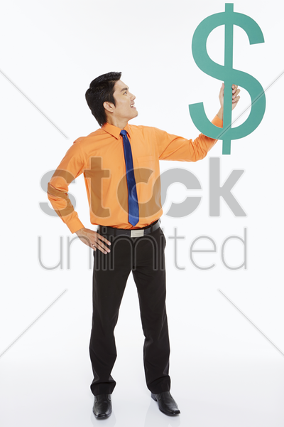 businessman holding up a dollar sign stock photo