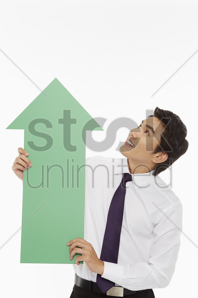 businessman holding up a green arrow stock photo
