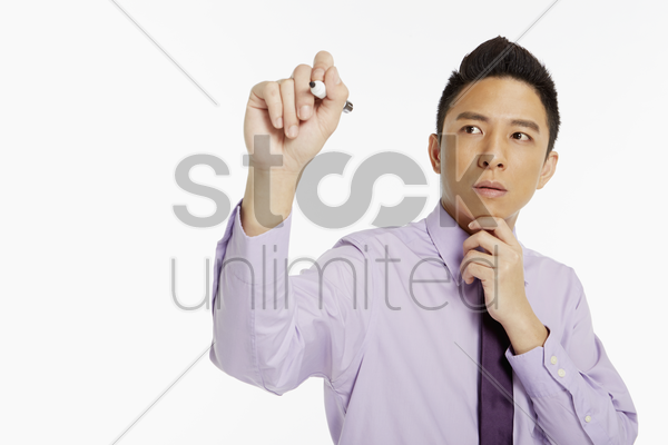 businessman holding up a marker pen, writing stock photo