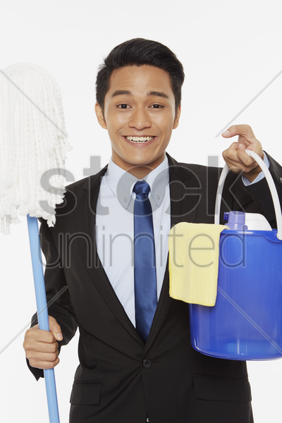 businessman holding up a mop and other cleaning supplies stock photo
