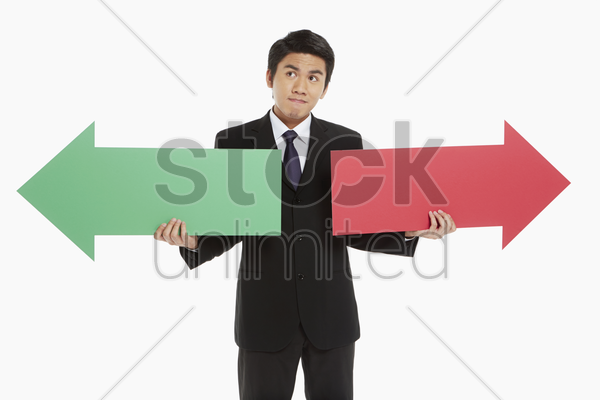 businessman holding up a red and green arrow stock photo
