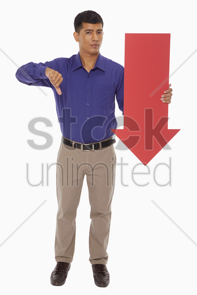 businessman holding up a red arrow, with thumbs down stock photo