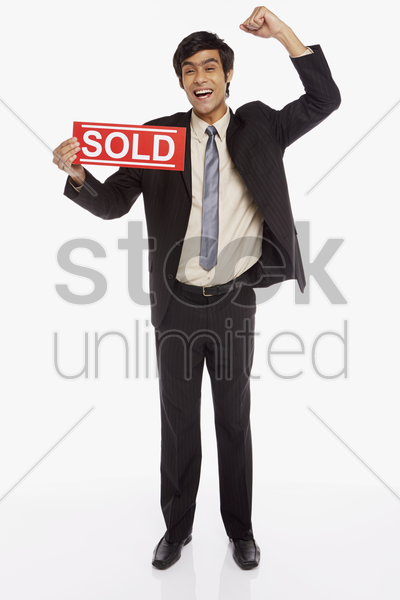 businessman holding up a 'sold' sign, cheering stock photo