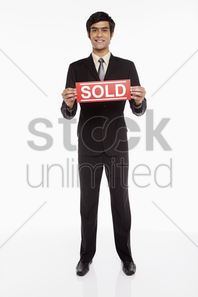 businessman holding up a 'sold' sign stock photo