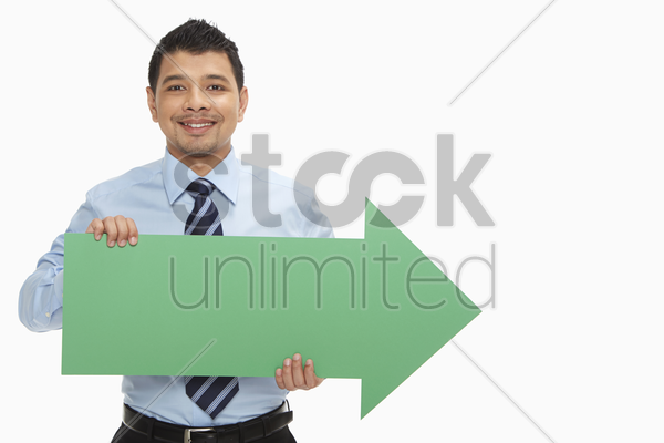 businessman holding up an arrow, pointing to the left stock photo
