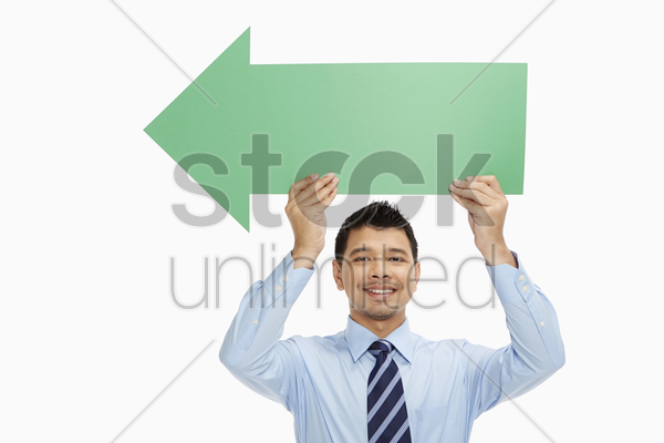 businessman holding up an arrow, pointing to the right stock photo
