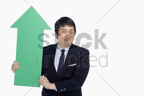 businessman holding up an arrow, pointing upwards stock photo