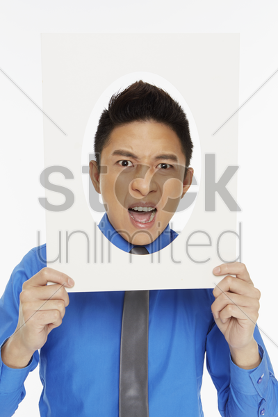 businessman holding up an oval frame, looking angry stock photo
