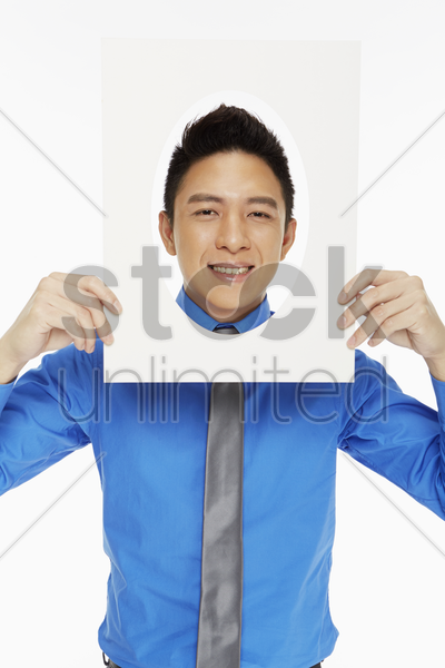 businessman holding up an oval frame, smiling stock photo