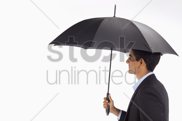 businessman holding up an umbrella stock photo