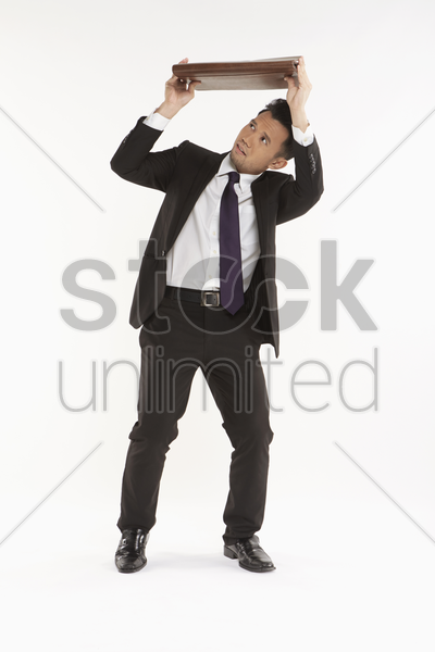 businessman holding up his briefcase stock photo