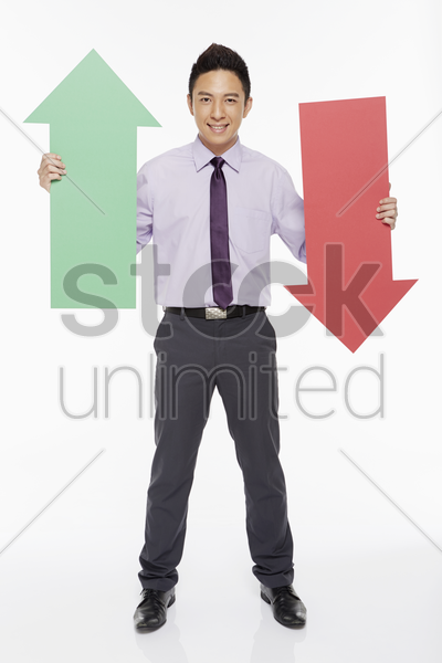 businessman holding up two arrows stock photo