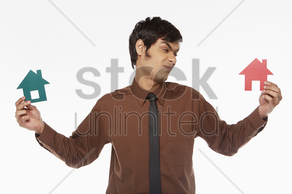 businessman holding up two cut out houses, contemplating stock photo