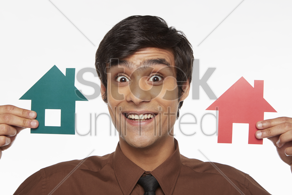 businessman holding up two cut out houses, smiling stock photo