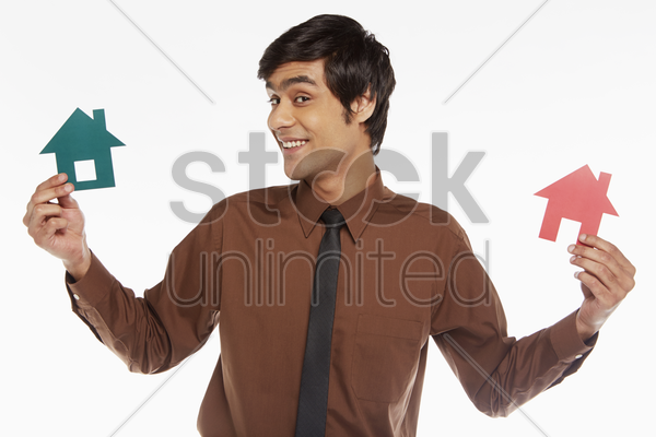businessman holding up two cut out houses stock photo