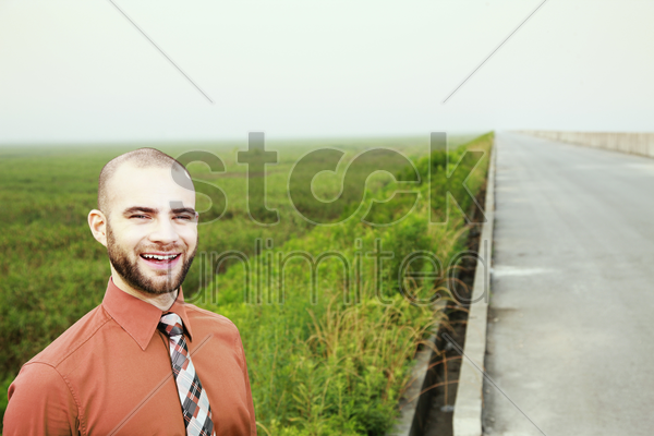 businessman in green with field in the background stock photo