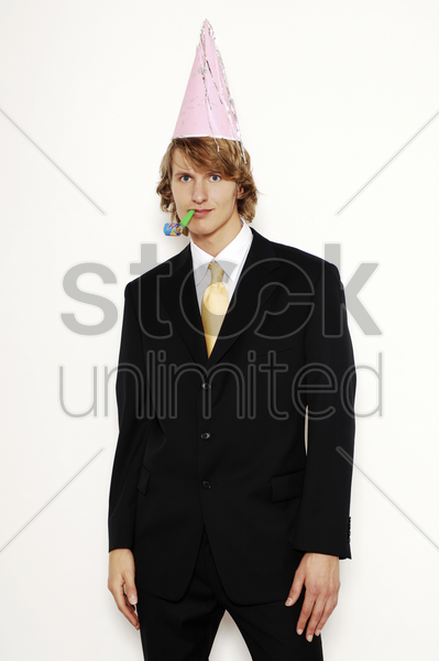 businessman in party hat blowing blowout stock photo