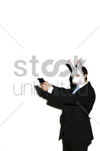 businessman in rabbit mask aiming a pistol stock photo