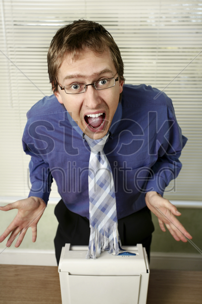 businessman in shock after looking at his shredded tie stock photo