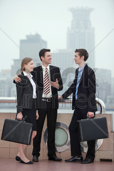 businessman introducing his partner to another businessman stock photo