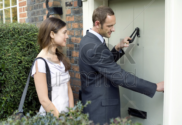 businessman knocking on the door while businesswoman waits by the side stock photo