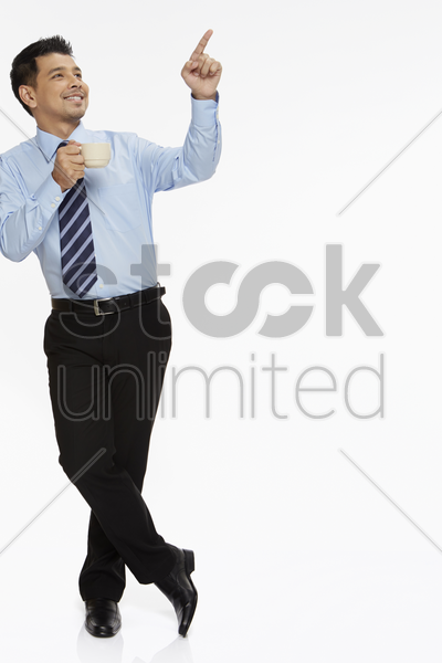 businessman leaning against a wall, having a drink stock photo