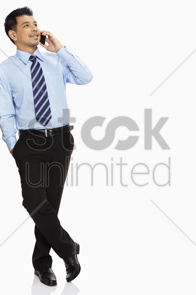businessman leaning against a wall, talking on mobile phone stock photo